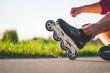 Leinwanddruck Bild - Woman laces roller skating for inline skating. Teenager rollerblading outdoors.