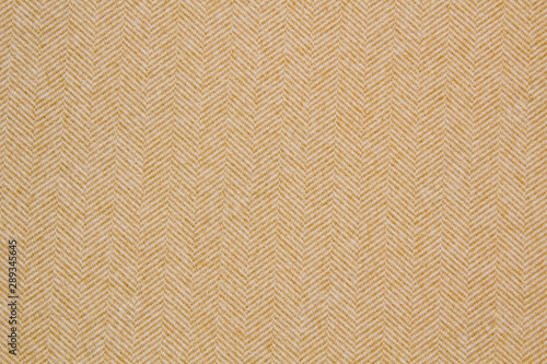 Obraz Cloth coats melange. The texture of the coat fabric close-up. Yellow herringbone fabric - fototapety do salonu