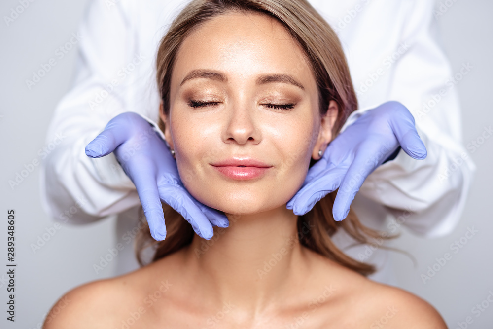 Fototapeta Close up portrait of young blonde woman with cosmetologyst hands in a gloves. Preparation for operation or procedure. Perfect skin, spa and care
