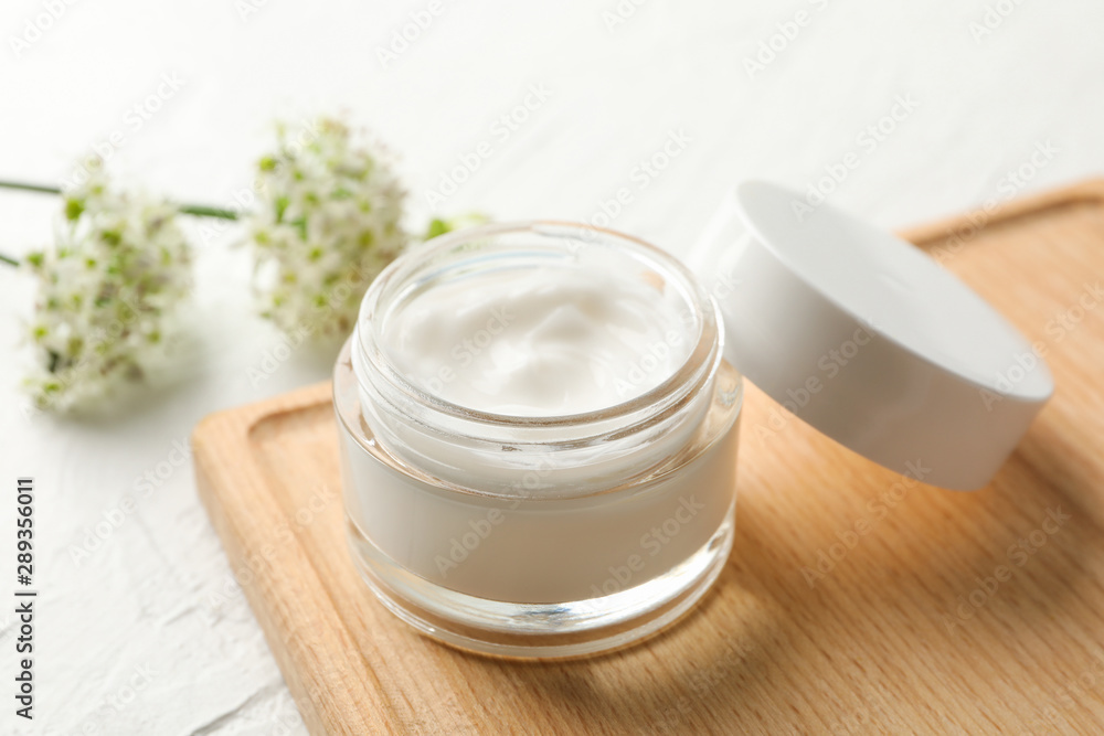 Fototapeta Jar with cream, allium flowers and board on white background, closeup