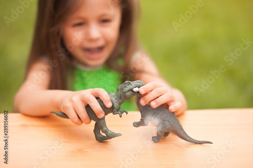 Cute little girl having fun playing with a toy dinosaurs Canvas Print
