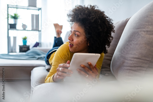 Attractive young woman using a digital tablet while relaxing on a sofa at home Tablou Canvas