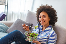 Cheerful Young Afro American Woman Eating Vegetable Salad At Home. Close-up Of Beautiful African American Woman Eating Salad At Home. Beautiful Woman On The Sofa Eating A Healthy Salade
