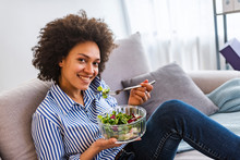 Beautiful Young Woman Having A Fresh Healthy Meal In The Living Room. Smiling Young Woman Eating Salad In The Living Room At Home, Healthy Food And Nutrition Concept