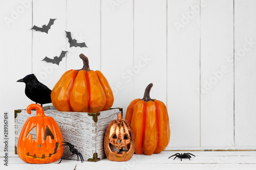 Photo Stands Coffee bar Halloween display with jack o lantern decor and pumpkins against a rustic white wood background. Copy space.