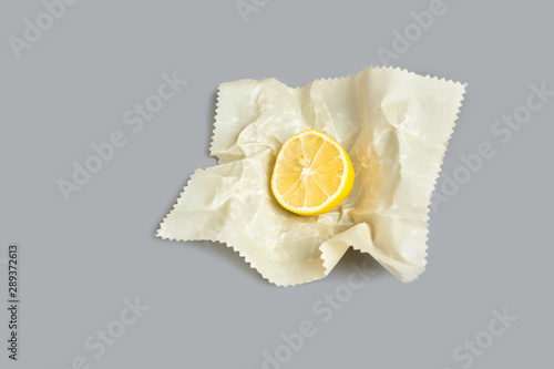 Photo Sliced lemon half in cloth beeswax food storage wrap / ecological alternative to