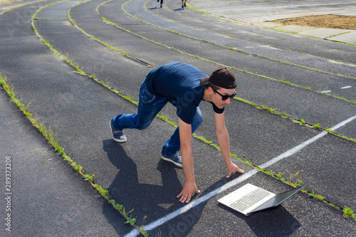Freelancer with a laptop at the start of the running track of the stadium Canvas Print