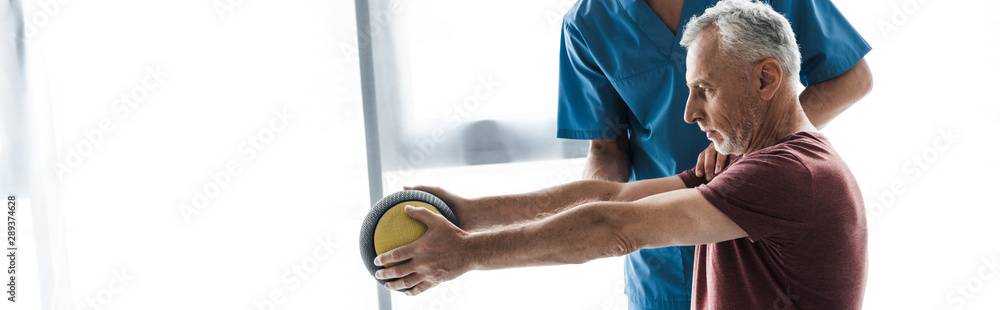 Fototapety, obrazy: panoramic shot of middle aged man exercising with ball near doctor