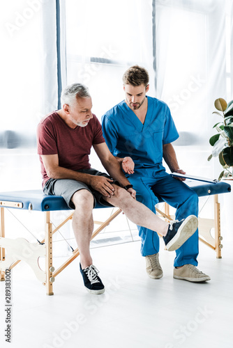 bearded mature patient touching leg near doctor holding clipboard in clinic