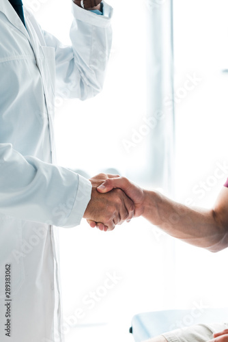 cropped view of doctor in white coat shaking hands with patient