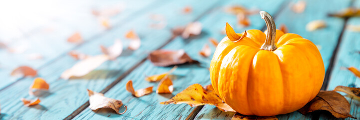 Autumn Background - Mini Pumpkin On Rustic Blue Table With Leaves And Sunlight