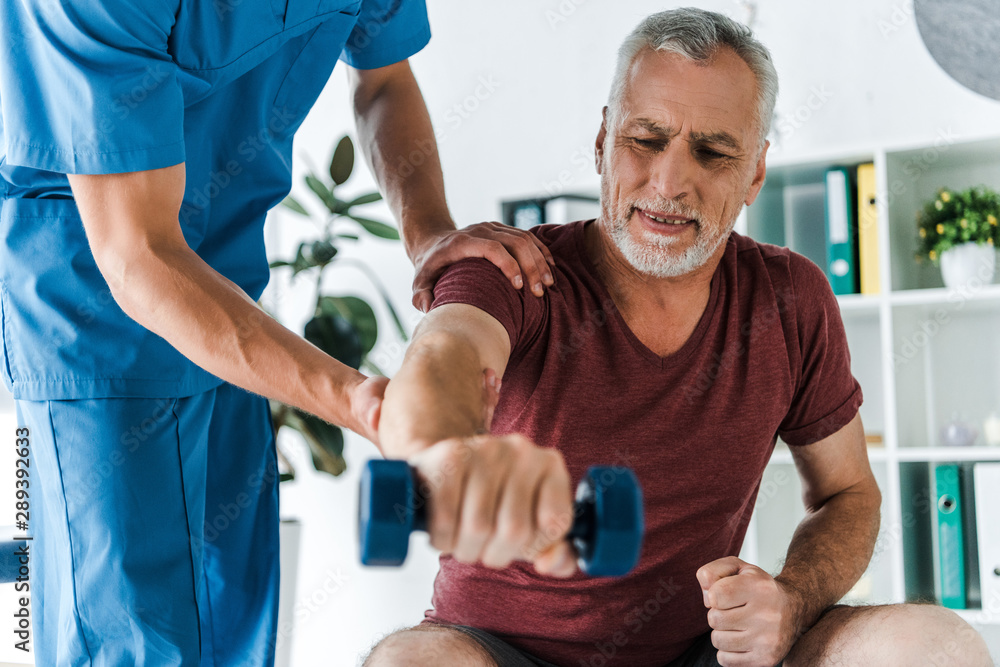 Fototapeta selective focus of mature man working out with dumbbell near doctor