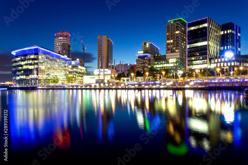 Obraz Manchester Skyline at Salford Quays Illuminated at Night and Reflected in the Water - fototapety do salonu