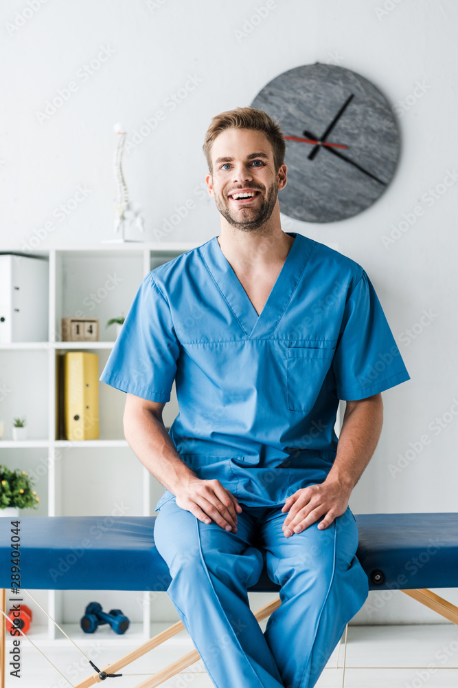 happy doctor looking at camera while sitting in clinic