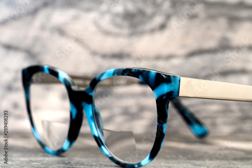 Eyeglasses Glasses with Bifocals and Black Blue Frame Fashion Vintage Style on Wood Desk Background, Rustic Still Life Style Wallpaper Mural