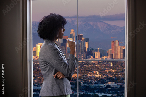 Black female businesswoman looking worried or tired by an office window with a view of downtown Los Angeles, California Fototapeta