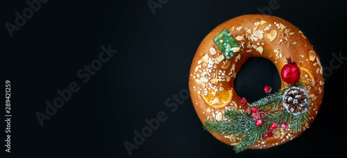 Fotomural Christmas round fruit cake decorated with fir tree branch, glazed fruits and nuts over  black background