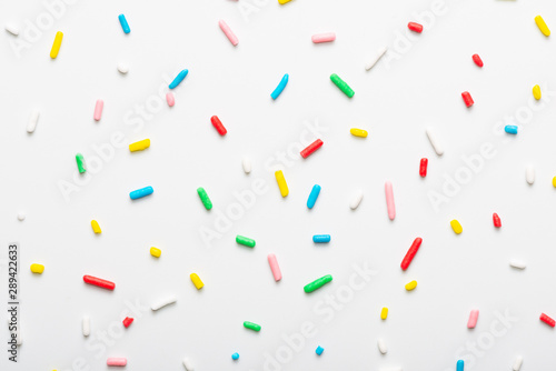 Fotografía flat lay of colorful sprinkles over white background, festive decoration