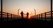 Lovers silhouette on bridge sunset time