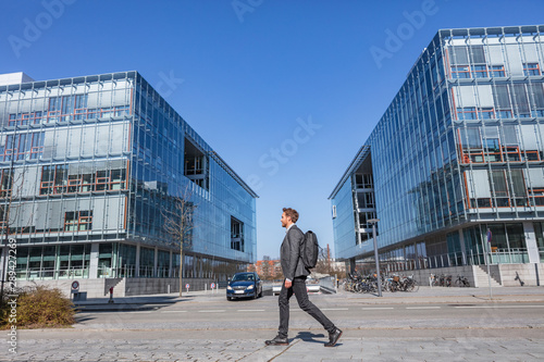 Young businessman commuter walking commuting to work going to office early morning on Copenhagen city street urban people commute lifestyle. Handsome man wearing suit in fall or spring.