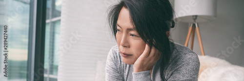 Sad depressed Asian woman having anxiety or depression during autumn season with seasonal affective disorder panoramic banner.