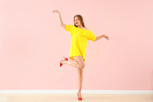 Beautiful Young Woman Dancing Against Color Wall