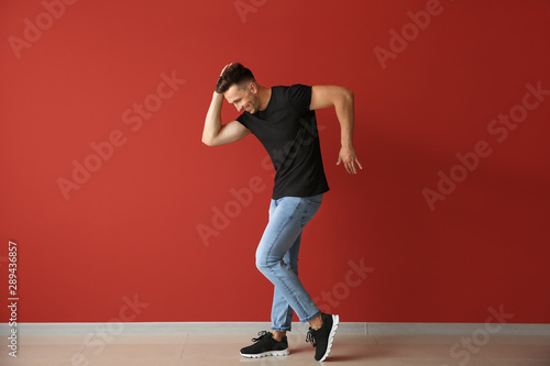 Fotografie, Obraz Handsome young man dancing against color wall