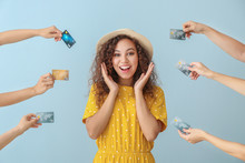 Young African-American Woman And Hands With Credit Cards On Color Background