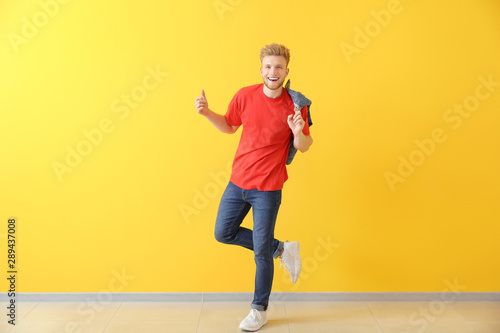 Poster Dance School Handsome young man dancing against color wall