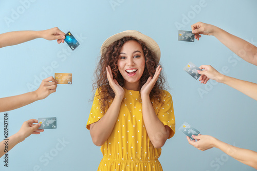 Cuadros en Lienzo  Young African-American woman and hands with credit cards on color background
