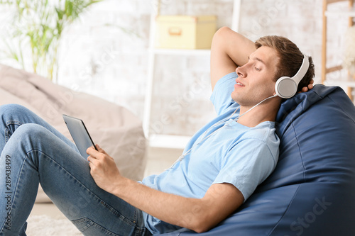 Young man relaxing and listening to music at home - 289438499