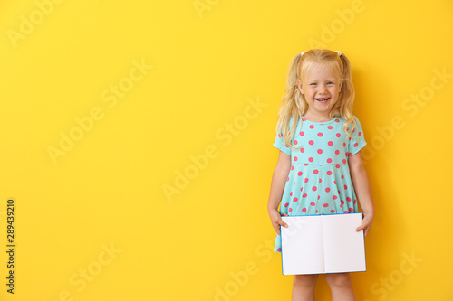 Obraz Cute little girl with book on color background - fototapety do salonu