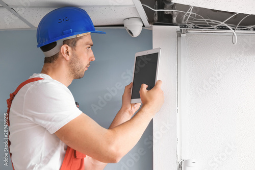 Electrician with tablet computer installing alarm system indoors