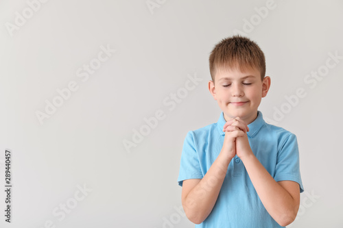 Photo Praying little boy on light background