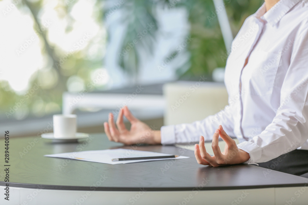 Fototapeta Young businesswoman meditating at workplace in office