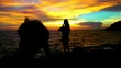 4K Wide shot of silhouette young adult romantic couple man taking photo with digital camera of woman girlfriend standing at rocky coastline at sunset with twilight sky in summer travel vacations.