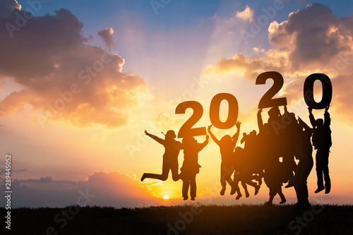Obraz Silhouette of Business teamwork hands up and jump to the beautiful golden sky from text 2020 background .The concept of business sucess,victory,achieve target goal,busness growth. - fototapety do salonu