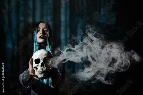 Woman with blue hair holding a skull with smoke Wallpaper Mural