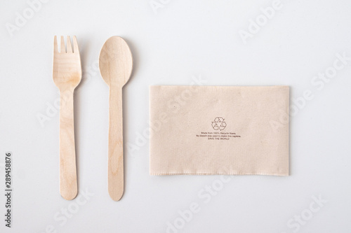 Obraz na plátně Recycle eco friendly disposable wood spoon fork and napkin paper in top view isolated on white table background