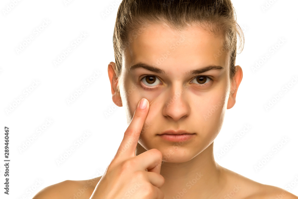 Fototapeta Young woman pulling her lower eyelid with her finger on white background