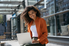 Portrait Of Beautiful African American Businesswoman Using Laptop Computer And Internet, Typing On Keyboard. Successful Business And Career. Smiling Woman Copywriter Working Freelance Project Outdoors