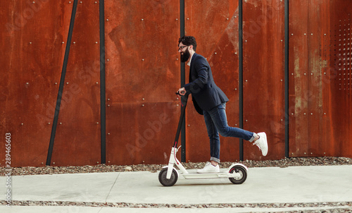 Fotografering  Cheerful hipster riding electric scooter