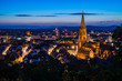 Germany, Freiburg im breisgau city in black forest nature with illuminated ancient historical muenster church surrounded by houses, aerial perspective by night