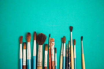Set of paint brushes on the turquois background