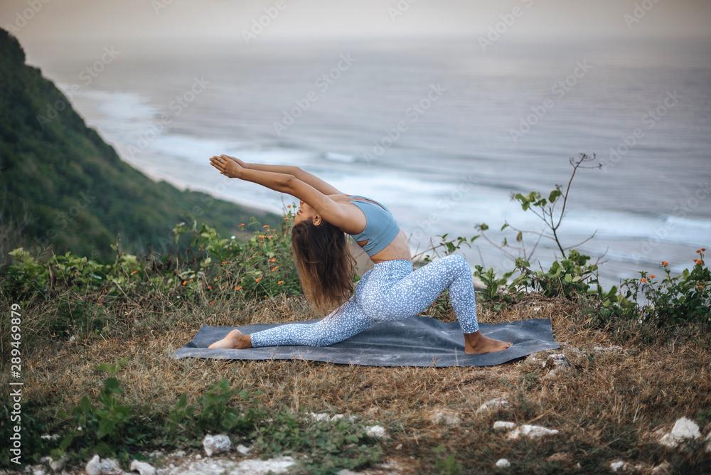 Fototapeta Girl practice yoga near ocean.