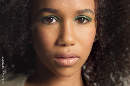 Fototapety, obrazy: closeup portrait of young mixed race model with curly hair. Face closeup with briight green makeup