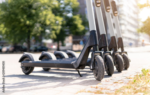 Electric kick scooters in city. E vehicle for rent. Urban modern transportation and technology concept. - 289481400