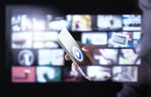 Movie Stream Smart App In Mobile Phone With Many Thumbnails Of Online Video Content. Man Watching Series With Smartphone. Futuristic Hologram Interface Around Screen. Subscribe To Entertainment.