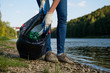 Volunteer woman collecting plastic rubbish on coast of the river. Cleaning environment concept