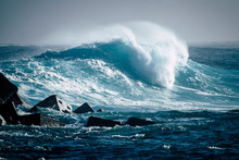 Great And Big Wave Breaking On Her In A Sea Or Ocean - Ocean Pacific Or Athlantic Blue Sea With A Rocks On The Left